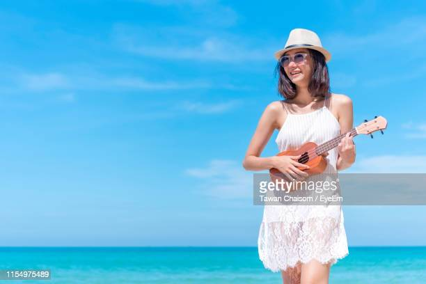 smiling young woman playing ukulele while standing at beach during summer - acoustic guitar stock pictures, royalty-free photos & images
