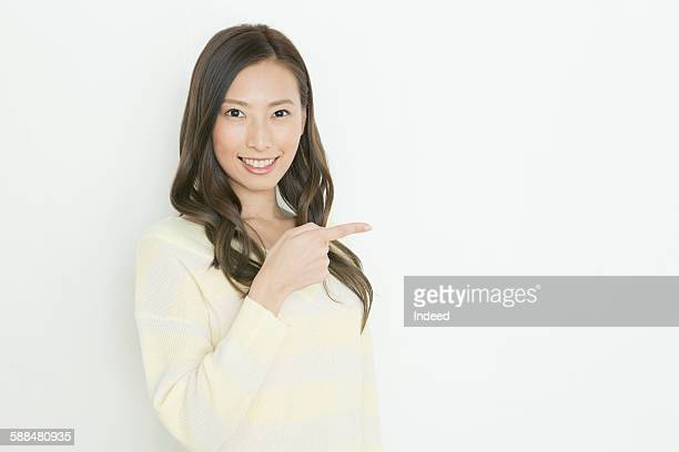 Smiling young woman pointing copy space
