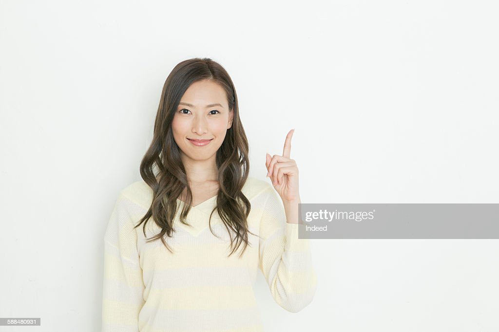 Smiling young woman pointing upward : Stock Photo