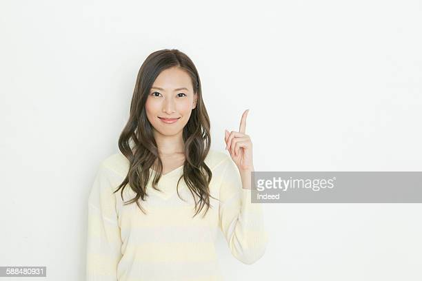 Smiling young woman pointing upward