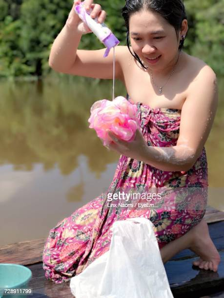smiling young woman pouring body lotion on loofah while kneeling at jetty over lake - loofah stock photos and pictures