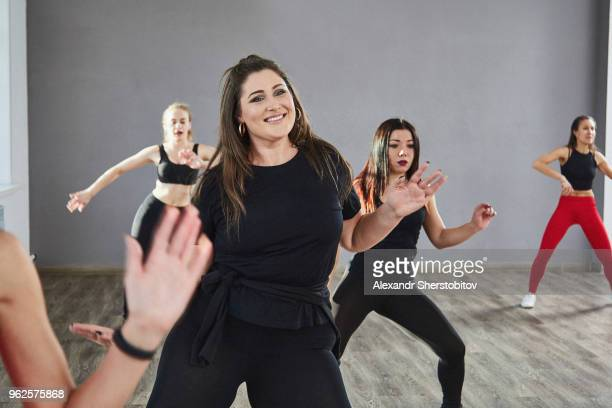 Smiling young woman practicing with friends in dance studio