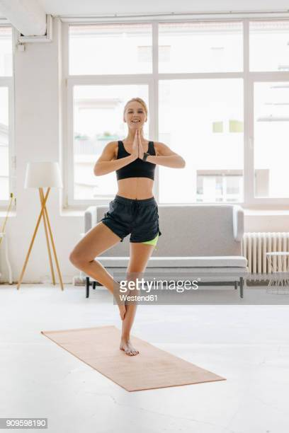 Smiling young woman practising yoga