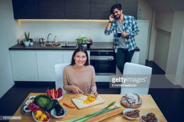 smiling young woman preparing food in the kitchen - raw food diet stock pictures, royalty-free photos & images