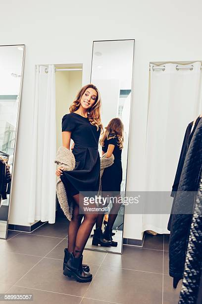 smiling young woman presenting new clothes in a boutique - black boot stock pictures, royalty-free photos & images