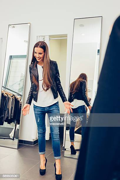 Smiling young woman presenting new clothes in a boutique