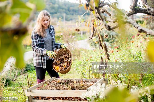 Smiling Young Woman Putting Leaves on Compost