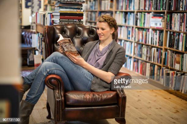 Smiling young woman reading book on armchair