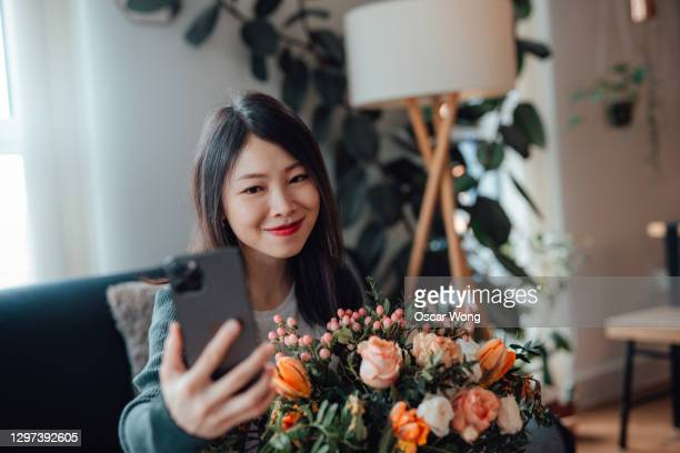 smiling young woman receiving flower bouquet delivery while having a video call on smartphone - flower stock pictures, royalty-free photos & images