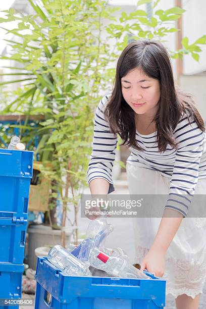 Smiling Young Woman Recycling Glass Bottles in Alley, Tokyo, Japan