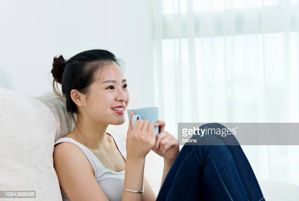 smiling young woman relaxing at home with cup of tea - sleeveless stock pictures, royalty-free photos & images