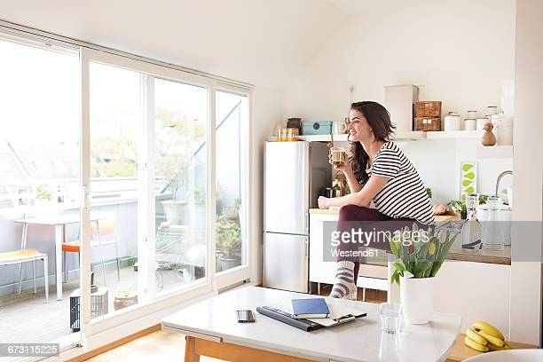 Smiling young woman relaxing in kitchen