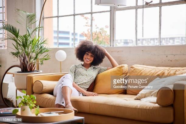 jeune femme de sourire détendant sur un sofa confortable à la maison dans l'après-midi - cheveux naturels photos et images de collection