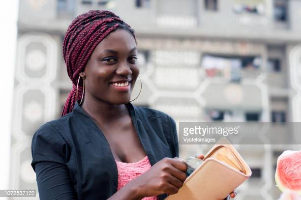 smiling young woman removing money from her purses. - côte d'ivoire stock pictures, royalty-free photos & images