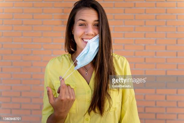 smiling young woman removing protective face mask - removing stock pictures, royalty-free photos & images