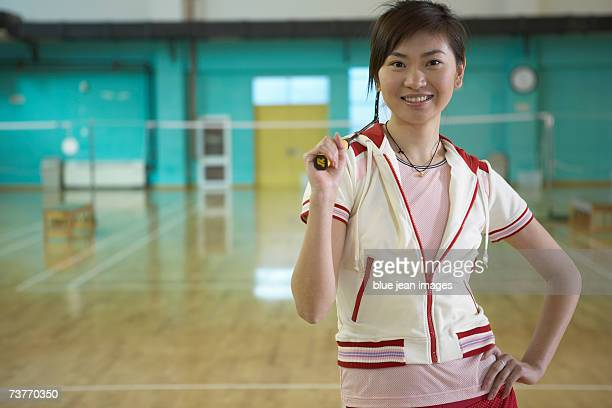 Smiling young woman rests her racket on her shoulder and relaxes during a game of badminton.