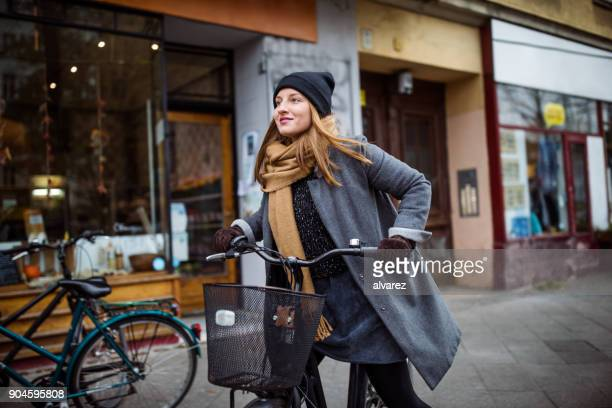 Smiling young woman riding bicycle by building
