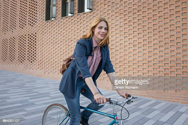 smiling young woman riding bicycle in the city - radfahren stock-fotos und bilder