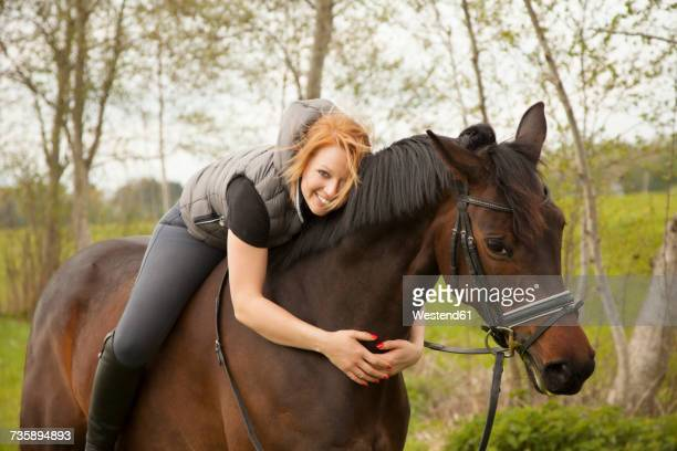 Smiling young woman riding horse