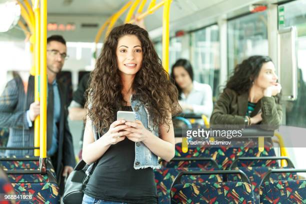 Smiling young woman riding in a bus