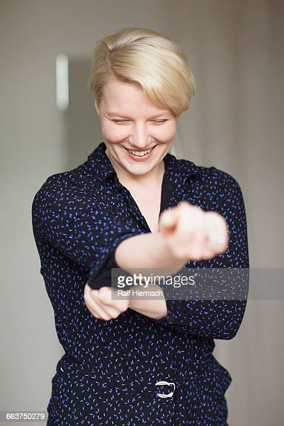 Smiling young woman rolling up her sleeves at home