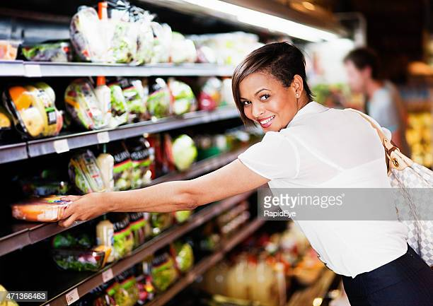 Smiling young woman selects healthy vegetables in supermarket