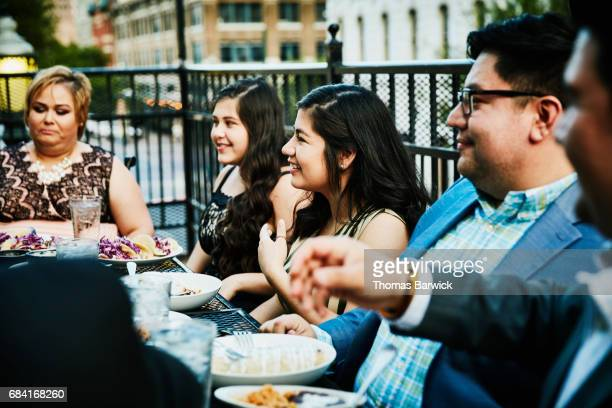 Smiling young woman sharing meal with family on restaurant deck