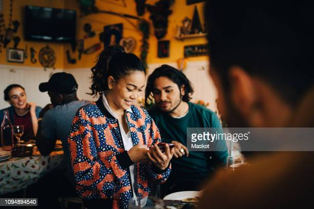 smiling young woman sharing smart phone with male friend while sitting at restaurant during dinner party - compartir fotografías e imágenes de stock