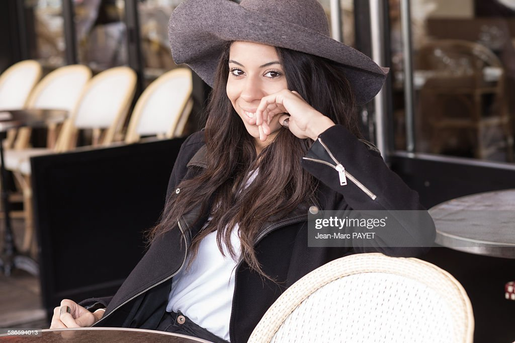 Smiling young woman sitting at a sidewalk cafe. : Photo