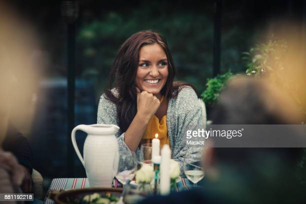 Smiling young woman sitting at dining table during party in back yard