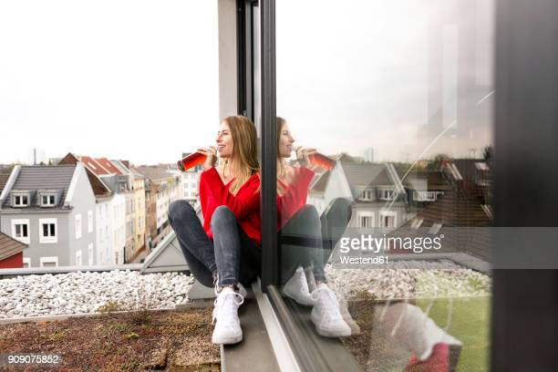 Smiling young woman sitting at the window in city apartment having a drink