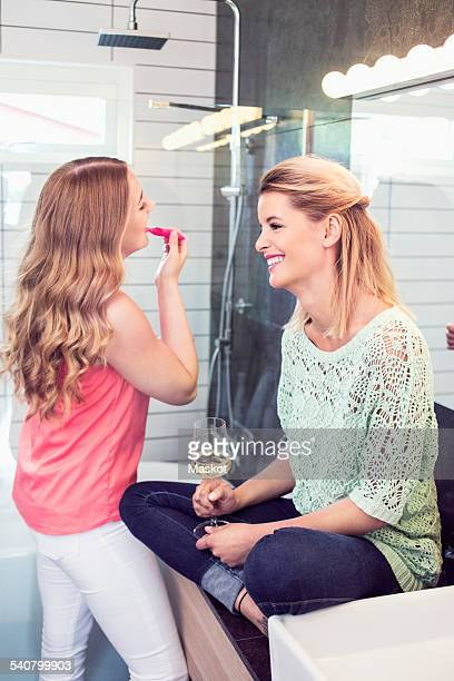 Smiling young woman sitting by sister applying lipstick in bathroom