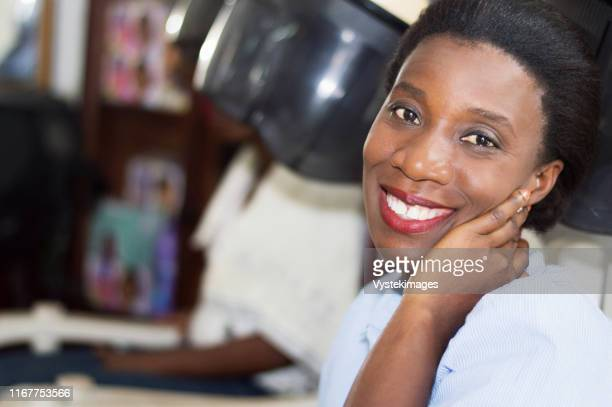 smiling young woman sitting in a hair salon waiting her turn. - côte d'ivoire stock pictures, royalty-free photos & images