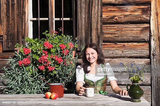 Smiling young woman sitting in front of Alpine cabin enjoying vacation