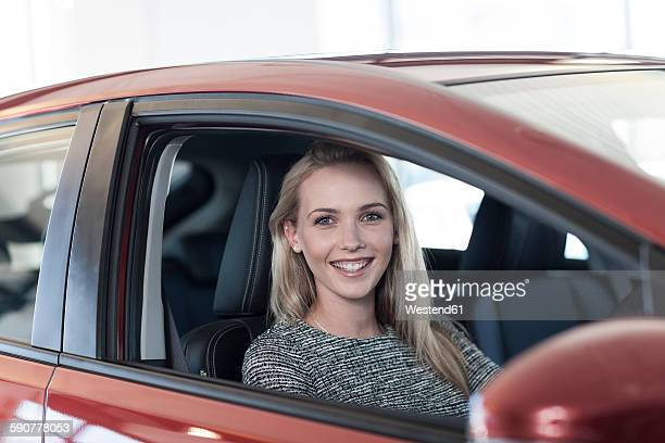 Smiling young woman sitting in new car