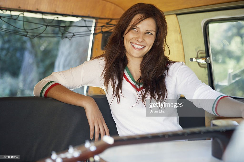 Smiling, Young Woman Sitting in the Back Seat of a Motor Home : Stock Photo