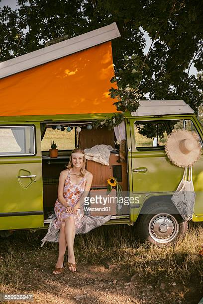 smiling young woman sitting in van in the nature - north rhine westphalia stock pictures, royalty-free photos & images