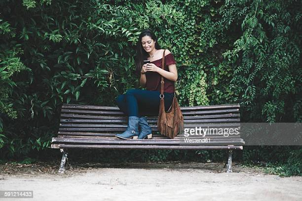 Smiling young woman sitting on a bench in park using cell phone
