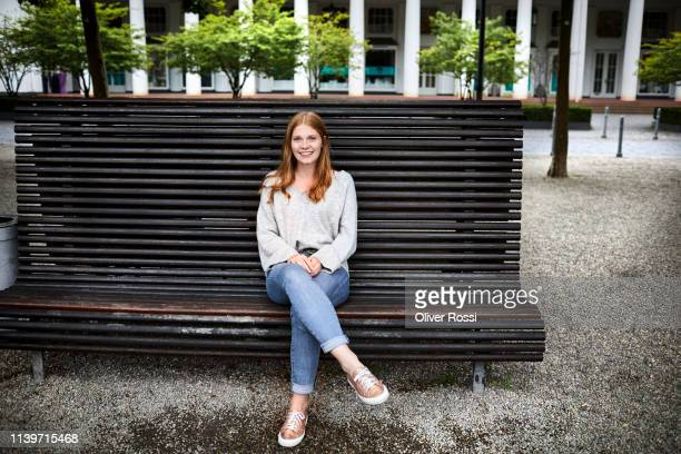 smiling young woman sitting on a bench - sitzen stock-fotos und bilder