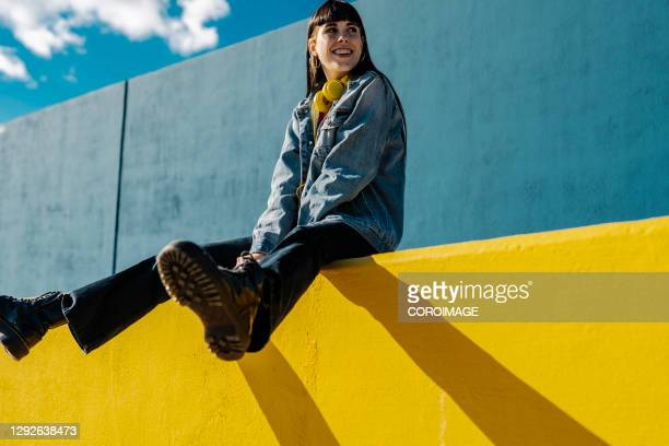 smiling young woman sitting on a yellow wall in sunny day - vida en la ciudad fotografías e imágenes de stock
