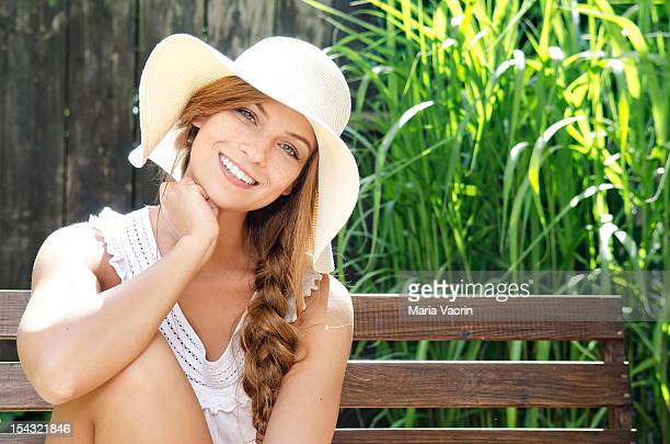 Smiling young woman sitting on bench, portrait