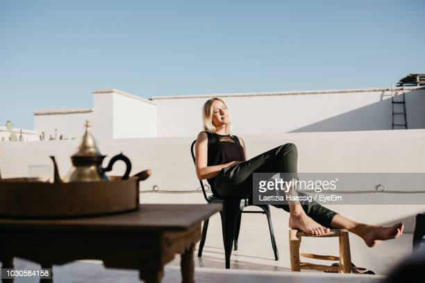 smiling young woman sitting on chair at building terrace - 屋根 ストックフォトと画像