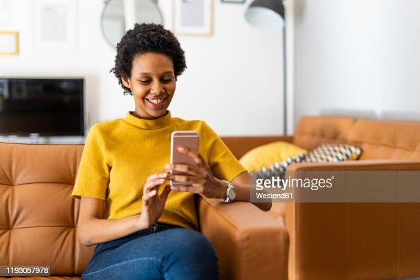 smiling young woman sitting on couch at home using smartphone - woman texting stockfoto's en -beelden
