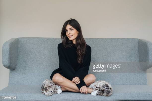 Smiling young woman sitting on couch wearing fluffy slippers