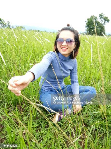 Smiling Young Woman Sitting On Grass