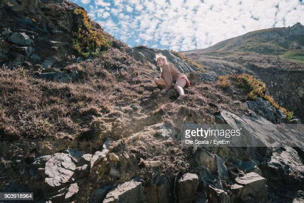 smiling young woman sitting on mountain against sky - sintra stock pictures, royalty-free photos & images