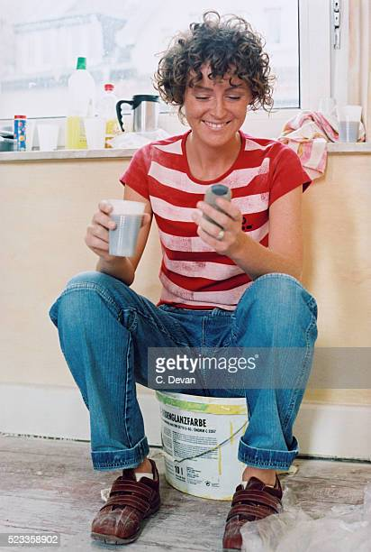 smiling young woman sitting on paint bucket using mobile phone - red trousers stock pictures, royalty-free photos & images