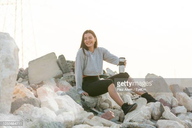 smiling young woman sitting on rock - aikāne stock pictures, royalty-free photos & images