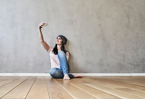 Smiling young woman sitting on the floor taking a selfie - gettyimageskorea
