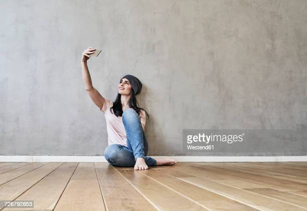Smiling young woman sitting on the floor taking a selfie